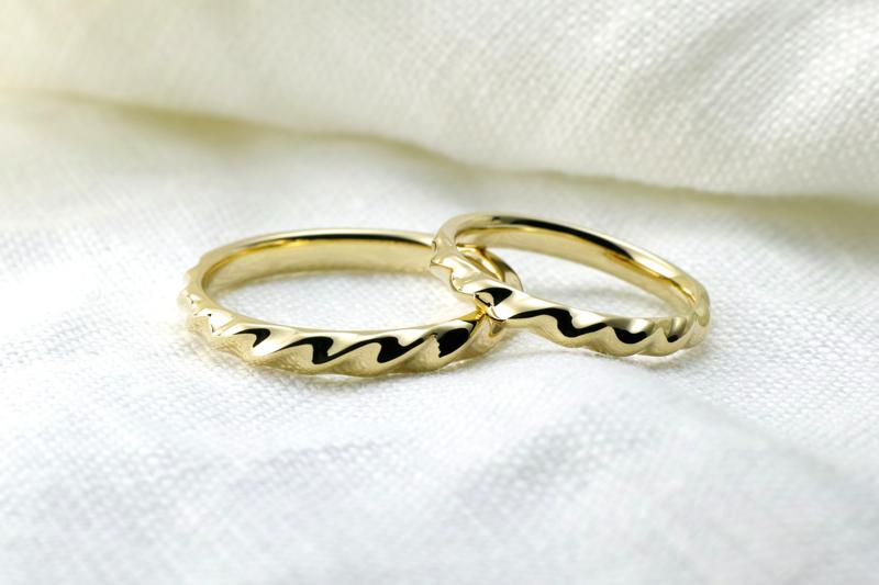 ゴールドをねじったようなフォルムが個性的な結婚指輪。何度も何度もねじられたデザインは、メビウスの輪のように永遠に途切れない想いが込められています。